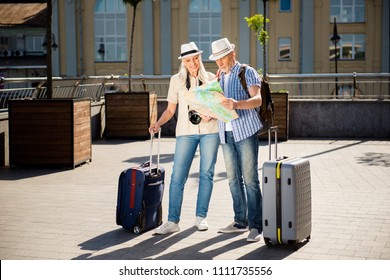 Portrait of two happy smiling grandma and granddad with bags photo camera in straw hats casual outfits holding map in hands searching for right road to destination