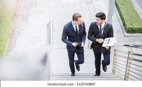 Portrait of two happy success handsome caucasian business man walk and talk on street sidewalk outdoor. Teamwork friendship business people entrepreneur partnership  greeting brainstorm concept banner