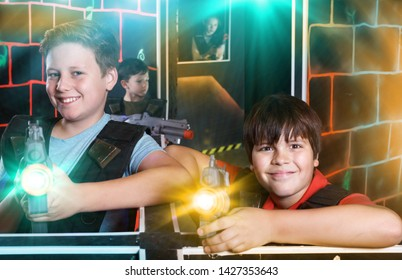 Portrait of two happy teen boys standing with laser guns ready for lasertag game indoors