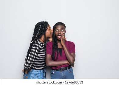Portrait of two happy young african women sharing secrets over white background