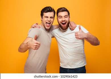 Portrait of a two happy young men showing thumbs up isolated over yellow background