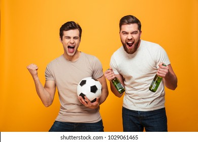 Portrait of a two happy young men holding beer bottles and soccer ball isolated over yellow background