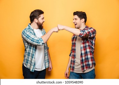 Portrait of a two happy young men giving fist bump isolated over yellow background