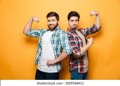 Portrait of a two happy young men standing and flexing biceps isolated over yellow background