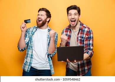 Portrait of a two happy young men holding laptop computer while standing with credit card and celebrating isolated over yellow background