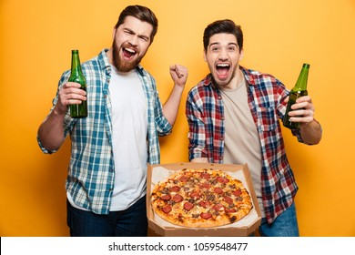 Portrait of a two happy young men drinking beer and eating pizza while standing isolated over yellow background