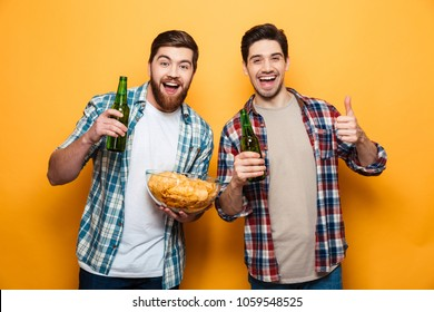 Portrait of a two happy young men drinking beer and eating snacks while standing isolated over yellow background