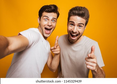 Portrait of a two happy young men best friends pointing fingers at camera taking a selfie isolated over yellow background