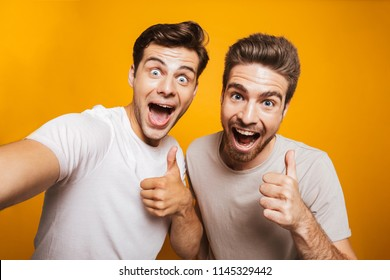 Portrait of a two happy young men best friends showing thumbs up taking a selfie isolated over yellow background