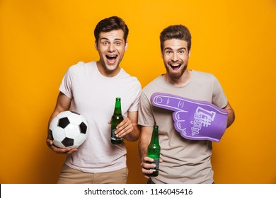 Portrait of a two happy young men best friends with soccer ball holding beer bottles and shouting isolated over yellow background