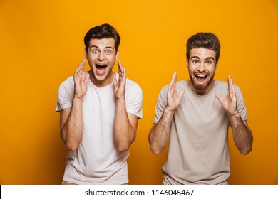 Portrait of a two happy young men best friends screaming loud isolated over yellow background