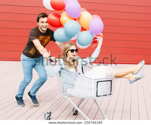 Portrait of two happy young people dating and having fun. Girl sitting in shopping cart and keeping color balloons in hand. Guy rolling trolley. Red background. Outdoors