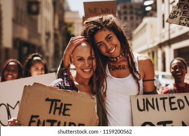 Portrait of two happy young woman with placards protesting outdoors with group of people in background.