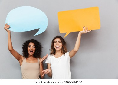 Portrait of two happy young women holding empty speech bubbles isolated over gray background