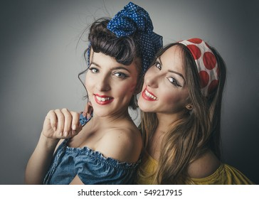 Portrait of two happy young women in retro style clothing with bandanas in friendly pose, studio background