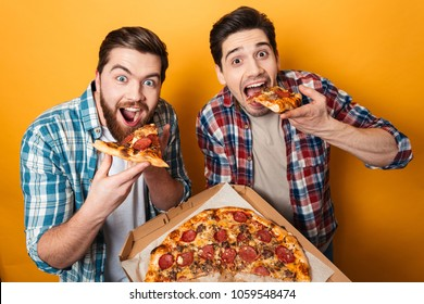 Portrait of a two hungry young men eating pizza isolated over yellow background