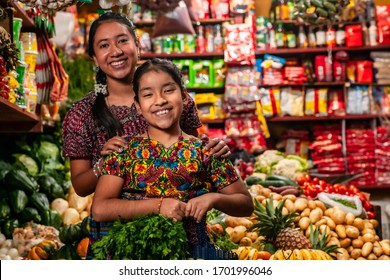 Portrait of two indigenous girls looking at the camera, in a grocery store of Guatemala.