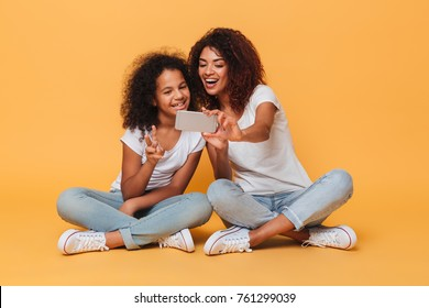 Portrait of a two joyful afro american sisters taking a selfie while sitting and showing peace gesture isolated over orange background