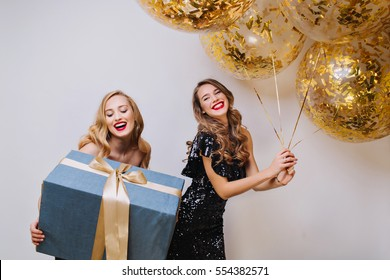 Portrait two joyful excited gorgeous women with long curly hair celebrating birthday party on white background Big present, balloons with golden tinsels, having fun,luxury dresses, laughing, happiness