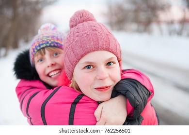 portrait of two joyful sisters on  street in   winter.