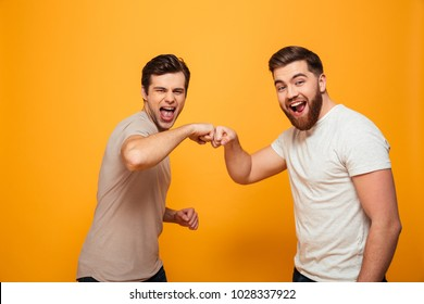 Portrait of a two joyful young men celebrating with a fist bump isolated over yellow background