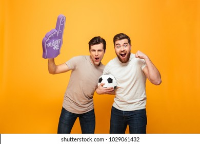Portrait of a two joyful young men holding soccer ball and foam glove isolated over yellow background