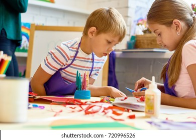 Portrait of two kids, boy and girl, making handmade gift cards in art and craft class at school