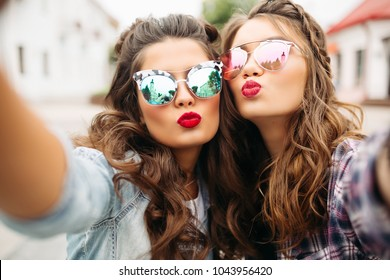 Portrait of two ladies with red lips and wavy hair making selfie wearing stylish mirrored sunglasses with duck faces in the street.