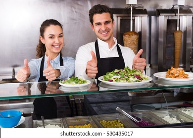 Portrait of two laughing workers with kebab at fastfood place