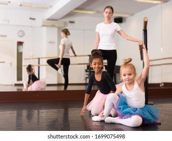 Portrait of two little girls and choreography teacher near ballet barre teacher in dance school