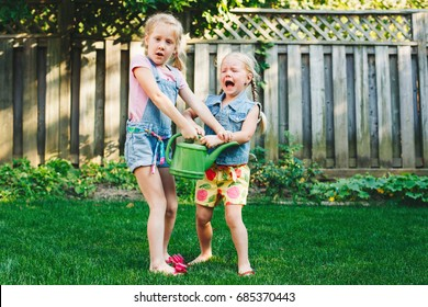 Portrait of  two little girls  sisters having fight on home backyard. Friends girls share watering pot can. Lifestyle family moment of siblings quarrel. Kids responsibility for doing home chores.