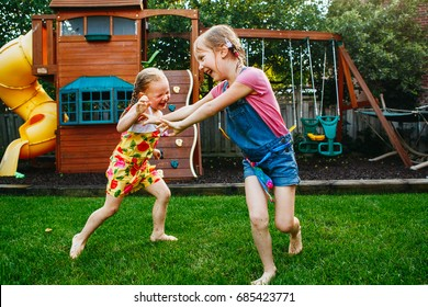 Portrait of  two little girls  sisters fighting on home backyard. Friends girls having fun. Lifestyle candid family moment of siblings quarreling playing together.