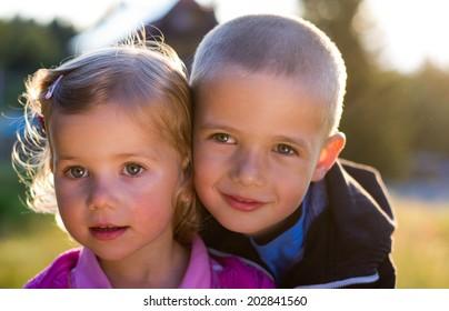 portrait of two little kids on summer garden background