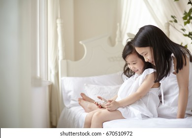 Portrait of two little sisters using tablet on bed.