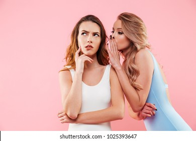 Portrait of a two lovely girls dressed in swimsuits whispering a secret isolated over pink background