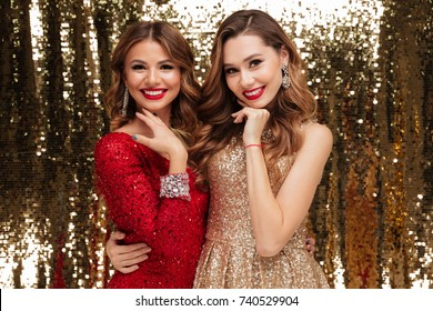 Portrait of two lovely pretty women in sparkly dresses hugging and looking at camera isolated over golden shiny background