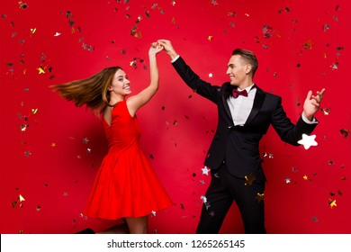 Portrait of two lovely slim graceful imposing elegant attractive positive people friends rejoicing flying star decorative elements having fun isolated on bright vivid shine red background