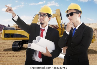 Portrait of two male engineers observe the construction site while wearing helmet and hold blueprint with excavator on the back