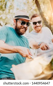 Portrait of two male friends cooking at barbeque grill.