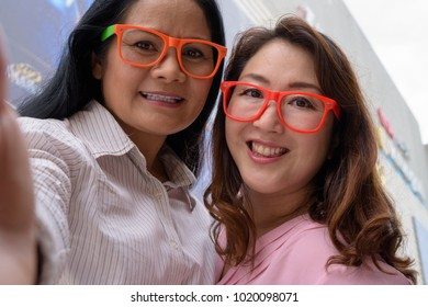 Portrait of two mature Asian women together outside the mall in Bangkok city