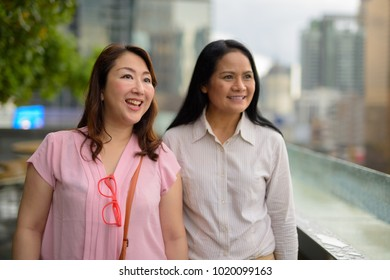 Portrait of two mature Asian women together against view of the city in Bangkok, Thailand
