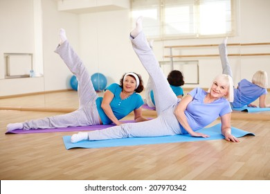 Portrait of two mature females doing physical exercise in sport gym