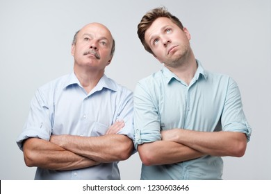 Portrait of two mature men with bored fed up expression, looks displeased up, being tired to explain their wifes where they were at night. Father and son are tired and bored to listen to bullshit