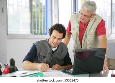 Portrait of two men in front of a laptop computer writing on a document
