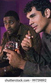 Portrait of two men holding drinks