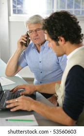 Portrait of two men in an office with a phone and a laptop computer