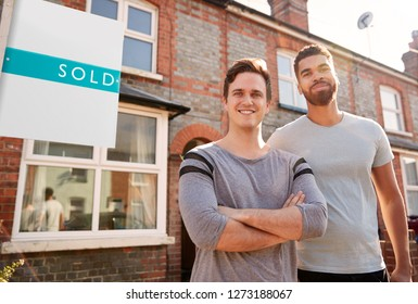 Portrait Of Two Men Standing Outside New Home With Sold Sign
