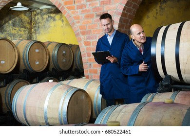 portrait of two men wine makers wearing coats standing with cardboard in winery cellar