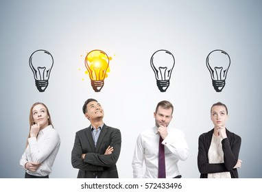 Portrait of two men and two women thinking about business near a gray wall. Light bulbs are drawn above their heads. One man has an idea.