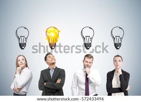 0eb00d00724 Portrait of two men and two women thinking about business near a gray wall.  Light